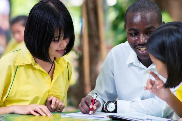 Afrikaanse buitenlandse leraar die eenvormige aziatische student onderwijst Premium Foto