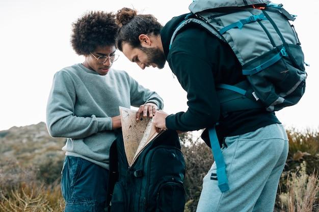 Afrikaanse en kaukasische jonge mannen die kaart in de rugzak zoeken Gratis Foto