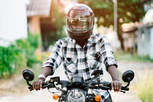 Afrikaanse fietser in de helm en bril rijden een motorfiets rijdt Premium Foto