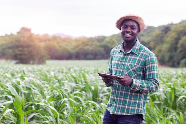 Afrikaanse landbouwerstribune in het groene landbouwbedrijf met holdingstablet Premium Foto