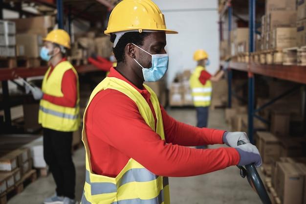 Afrikaanse magazijnmedewerker die leveringsdozen laadt terwijl hij veiligheidsmasker draagt - focus op gezicht Premium Foto