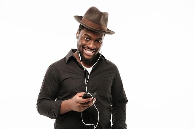 Afrikaanse man chatten via de telefoon en muziek luisteren Gratis Foto