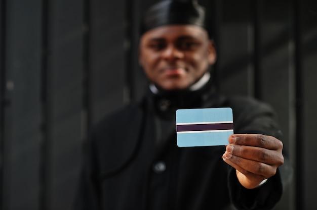 Afrikaanse man draagt zwarte durag houdt de vlag van botswana bij de hand geïsoleerde donkere muur. Premium Foto