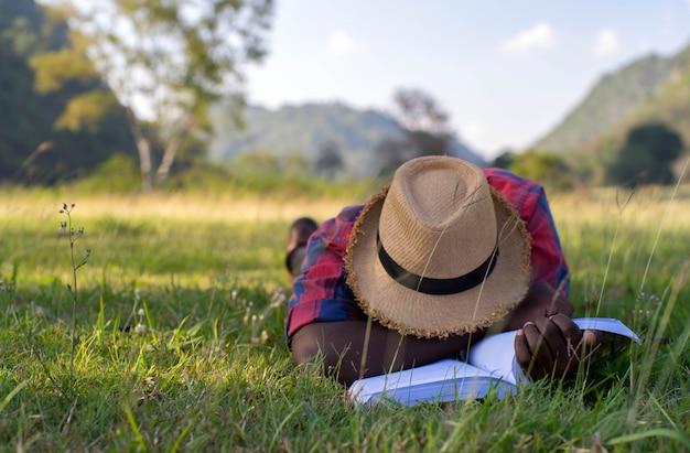 Afrikaanse mens die en na het lezen van een boek op het gras ligt slaapt. Premium Foto