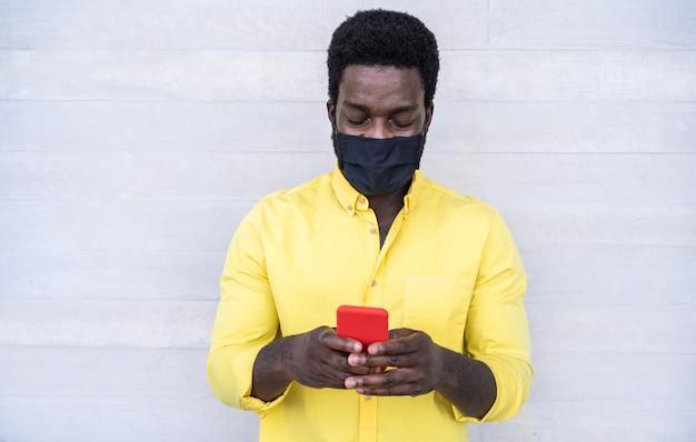 Afrikaanse mens die mobiele telefoon met behulp van terwijl het dragen van gezichts beschermend masker openlucht Premium Foto