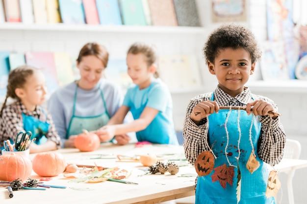 Afrikaanse schooljongen in blauw schort met stok met halloween decoraties gemaakt van droge bladeren die op draden hangen Premium Foto