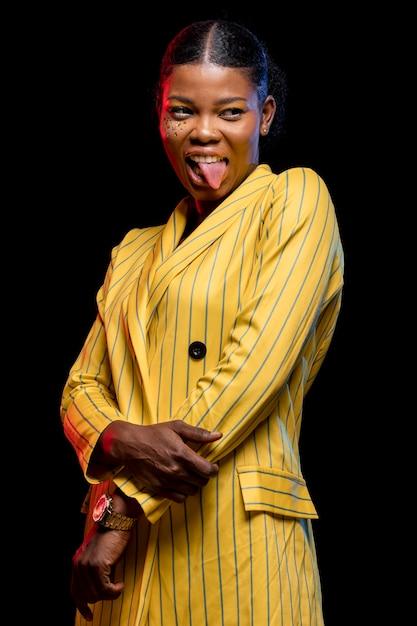Afrikaanse vrouw in geel jasje met haar tong uit Gratis Foto