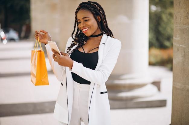 Afrikaanse vrouw met gele boodschappentassen Gratis Foto