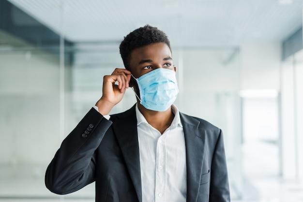 Afrikaanse zakenman draagt een mondbescherming om te voorkomen dat hij ziek wordt op het werk op kantoor Gratis Foto
