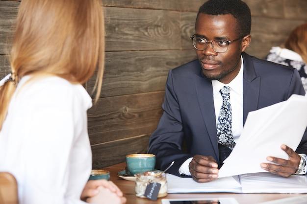 Afrikaanse zakenman interviewt blanke vrouwelijke kandidaat voor een secretarispositie Gratis Foto