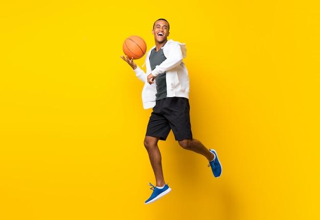 Afro amerikaanse basketbalspeler man op geel Premium Foto