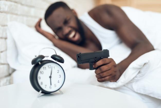 Afro-amerikaanse boze man wijzend op de wekker met het pistool. ochtend Premium Foto
