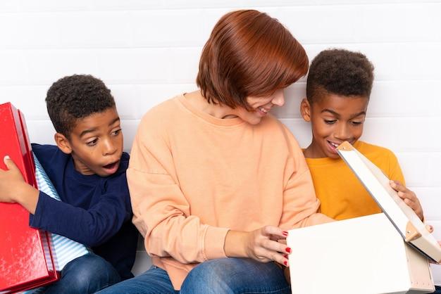 Afro-amerikaanse kinderen met hun moeder onder vele geschenken voor kerstvakantie Premium Foto