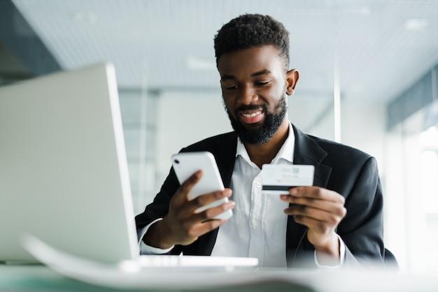 Afro-amerikaanse man betalen met creditcard online terwijl het doen van bestellingen via mobiel internet transactie met behulp van mobiele bank applicatie. Gratis Foto