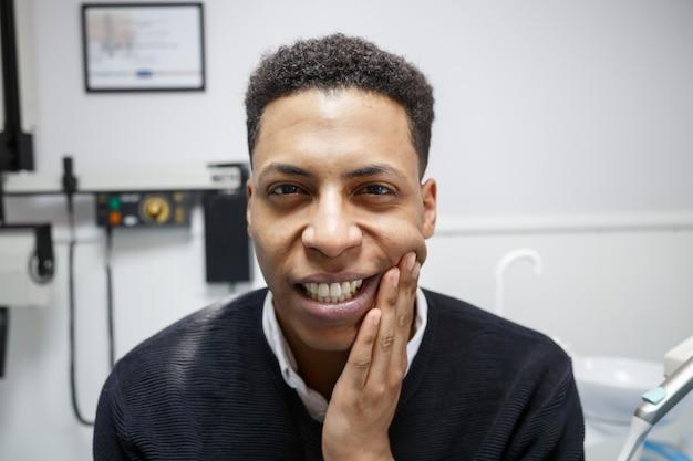 Afro-amerikaanse man die lijden aan kiespijn en klagen tijdens bezoek aan professionele tandarts. Premium Foto