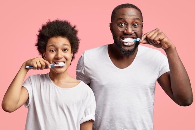 Afro-amerikaanse man en kind tanden poetsen Gratis Foto