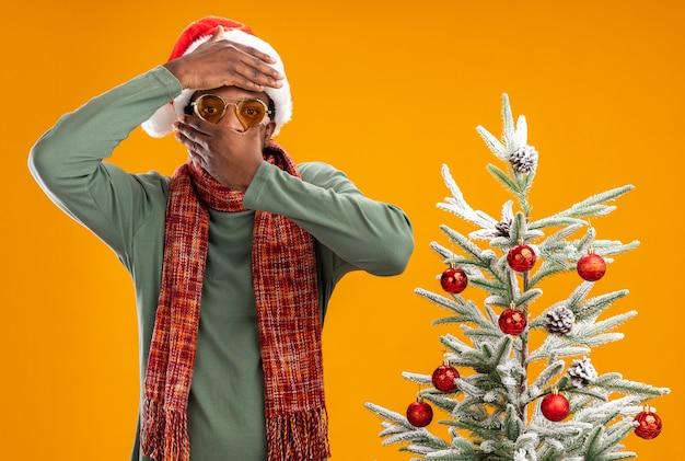 Afro-amerikaanse man in kerstmuts en sjaal rond de nek camera kijken met hand op zijn hoofd die mond bedekt met andere hand staande naast een kerstboom op oranje achtergrond Gratis Foto