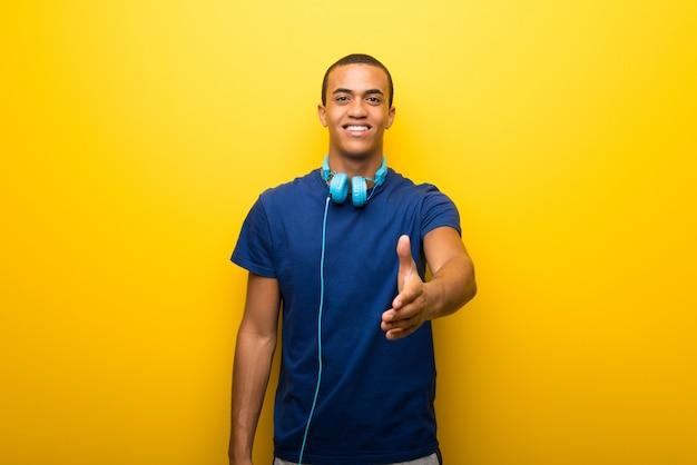 Afro-amerikaanse man met blauw t-shirt op gele achtergrond handen schudden voor het sluiten van een goede deal Premium Foto