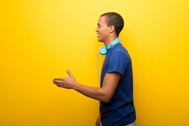 Afro-amerikaanse man met blauw t-shirt op gele achtergrond handshaking na goede deal Premium Foto