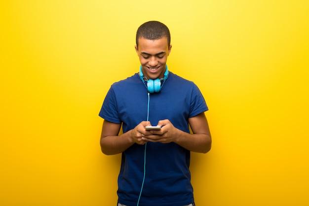 Afro-amerikaanse man met blauwe t-shirt op gele muur verzenden van een bericht of e-mail met de mobiel Premium Foto