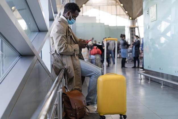 Afro-amerikaanse man met gezichtsmasker in luchthaven Premium Foto