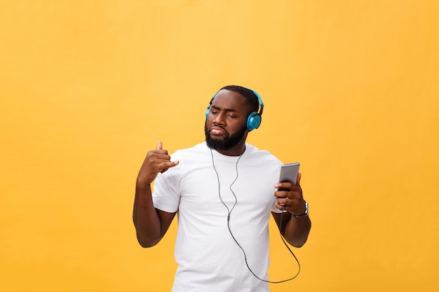 Afro-amerikaanse man met koptelefoon luisteren en dansen met muziek. geïsoleerd op gele achtergrond Premium Foto