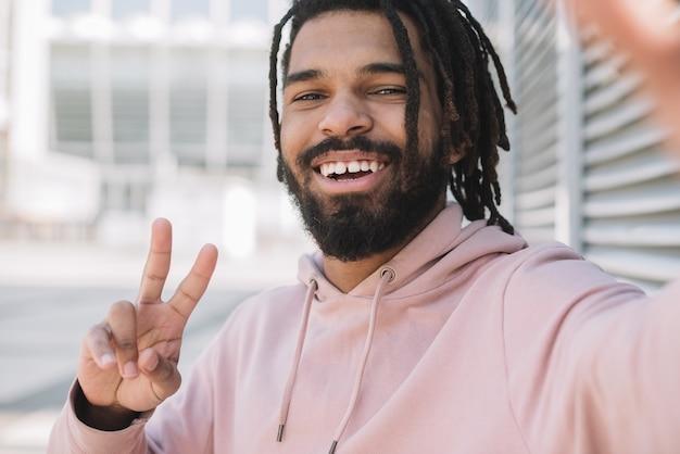 Afro-amerikaanse man met vredesteken Gratis Foto