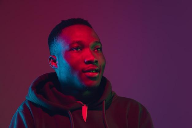 Afro-amerikaanse man portret geïsoleerd op verloop muur in neonlicht Gratis Foto