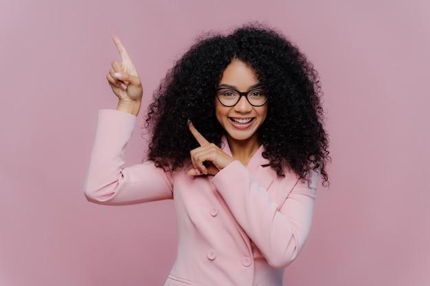 Afro-amerikaanse vrouw met donker bossig kapsel, draagt violet pak Premium Foto