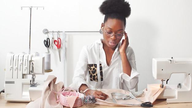 Afro-amerikaanse vrouw naaister, modeontwerper luisteren naar muziek via een koptelefoon tijdens het werken aan stof in de studio workshop Premium Foto