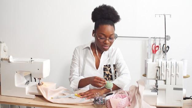 Afro-amerikaanse vrouw naait kleding in haar favoriete studio, werkplaats Premium Foto