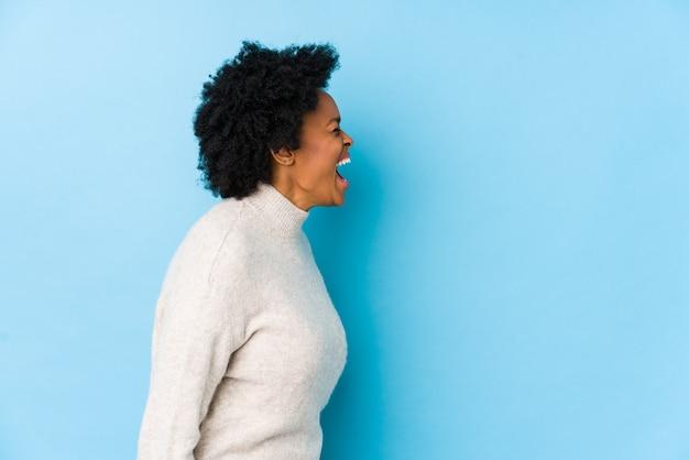 Afro-amerikaanse vrouw van middelbare leeftijd tegen een blauwe ruimte geïsoleerd schreeuwen naar een kopie ruimte Premium Foto