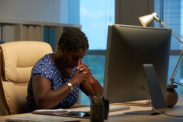 Afro-amerikaanse vrouw zit achter computer in kantoor en leunend hoofd op gevouwen handen Gratis Foto