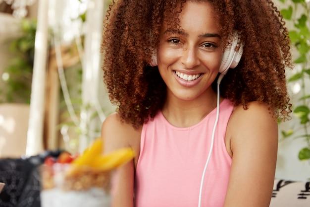 Afro-amerikaanse vrouwelijke student luistert naar liedjes uit de afspeellijst, geniet van perfect geluid in moderne koptelefoons, heeft een vrolijke uitdrukking, zit tegen het interieur van een café. mensen, vrije tijd, entertainmet concept Gratis Foto