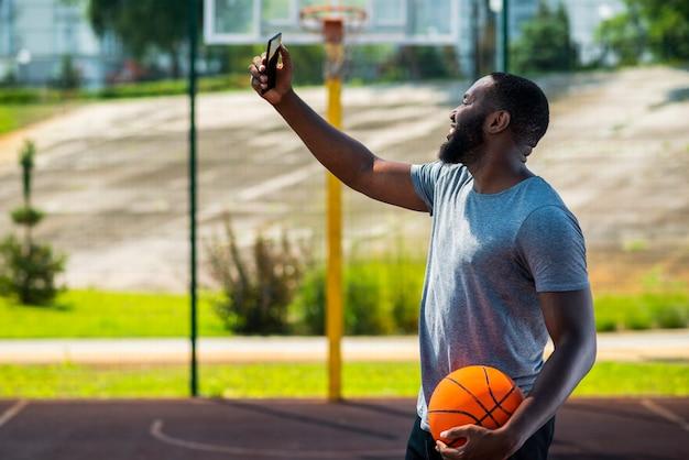 Afro basketbal man die een selfie met zijn telefoon Gratis Foto