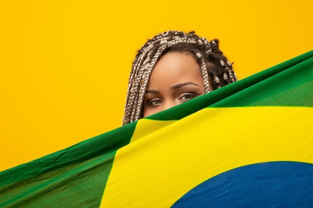 Afro-meisje juichen voor favoriete braziliaanse team, nationale vlag in het geel te houden. Premium Foto