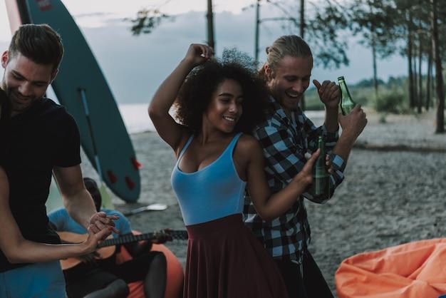 Afro-paren dansen op het strand. afro-gitarist. Premium Foto