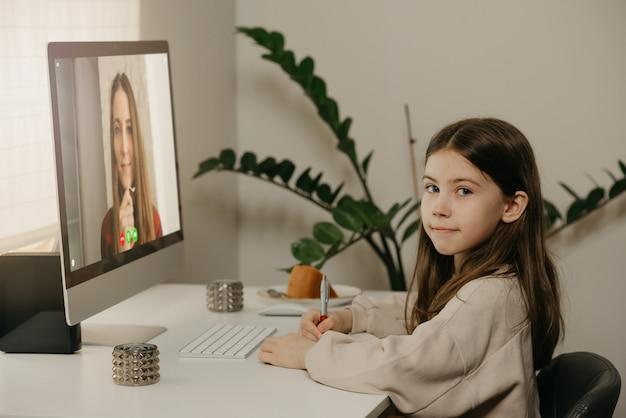 Afstand leren. een jong meisje met lang haar studeren op afstand van haar vrouwelijke leraar online. een mooi kind leert thuis een les met een desktopcomputer. thuisonderwijs. Premium Foto