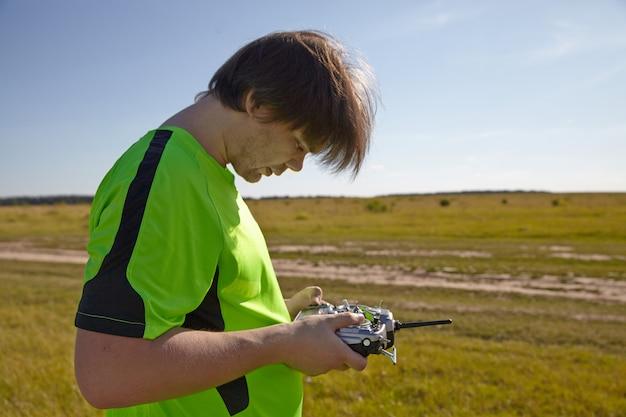 Afstandsbediening voor quadrocopter, close-up. zender voor het besturen van bewegend apparaat in mannelijke handen, onscherpe natuur achtergrond Premium Foto