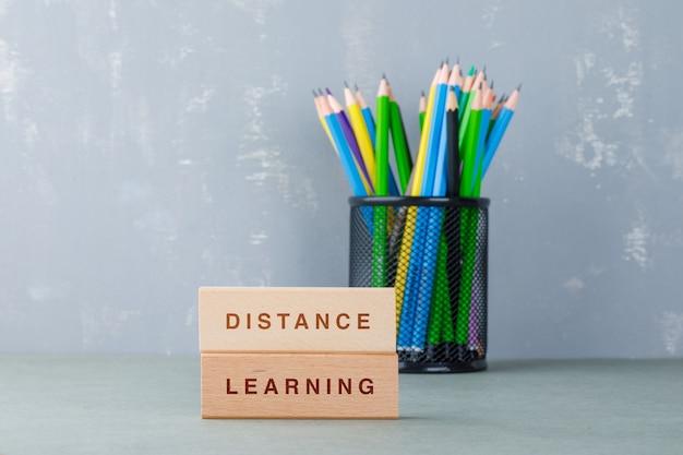 Afstandsonderwijs concept met houten blokken met woorden erop, kleurrijke potloden zijaanzicht. Gratis Foto