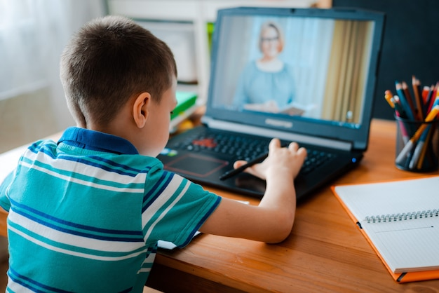 Afstandsonderwijs online onderwijs. een schooljongen studeert thuis en maakt huiswerk op school. een afstandsonderwijs thuis Premium Foto