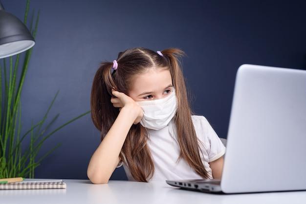 Afstandsonderwijs online onderwijs. schoolmeisje in medisch masker dat thuis bestudeert, bij laptop notitieboekje werkt en schoolhuiswerk doet. coronavirus quarantaineconcept Premium Foto