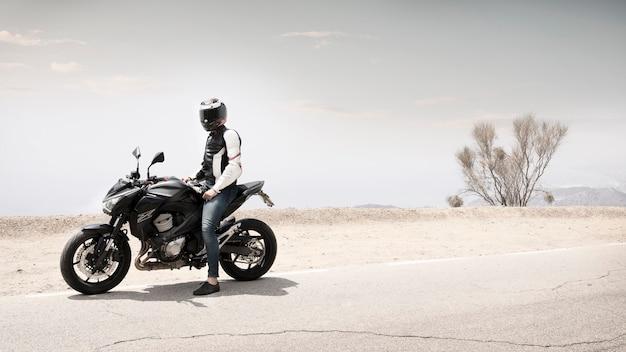 Afstandsschot motorcylist man zittend op motor Gratis Foto
