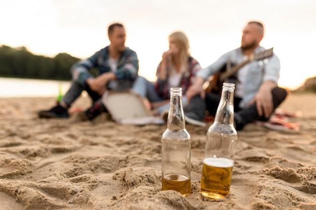 Afstandsschot ongericht groep mensen met twee flessen bier Premium Foto