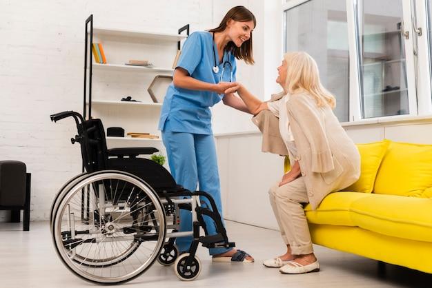 Afstandsschot verpleegster die oude vrouw helpt die opstaat Gratis Foto