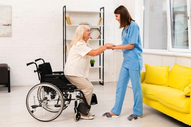 Afstandsschot verzorger die oude vrouw helpt Gratis Foto