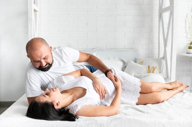 Afstandsschoten ouders knuffelen in bed Gratis Foto