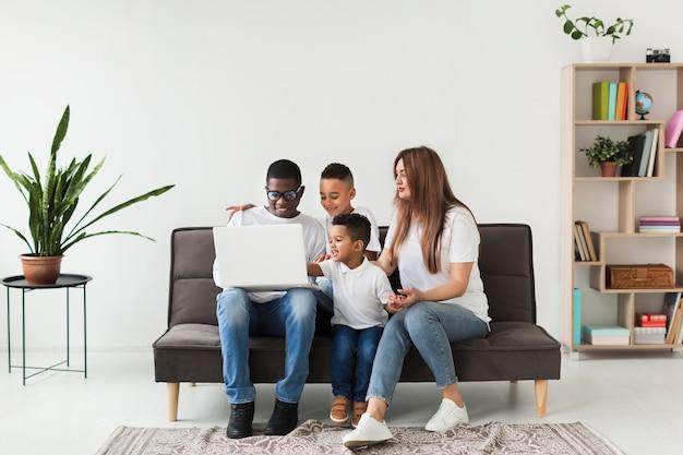 Afstandsschotfamilie die op laptop kijkt Gratis Foto