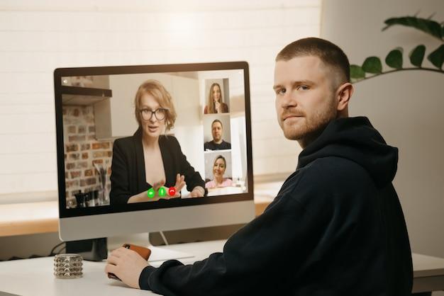 Afstandswerk. een achteraanzicht van een man tijdens een videogesprek met zijn collega's op de desktopcomputer. een man leidde thuis af van een online briefing. Premium Foto