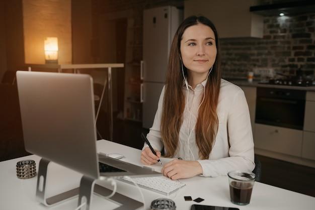 Afstandswerk. een blanke vrouw met koptelefoon op afstand werken op haar laptop. een gelukkig donkerbruin meisje met een glimlach die nota's doet tijdens een online bedrijfsbriefing op haar gezellige huiswerkplaats. Premium Foto